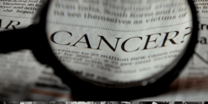 magnifying glass over the word cancer