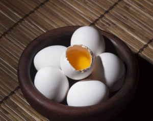 A bowl of six eggs, one cracked open