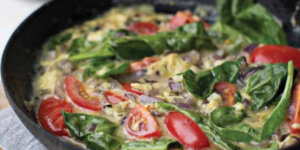 A cast iron skillet with a tomato and spinach frittata