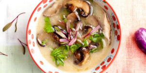 Bowl of soup with mushrooms and herbs on a table