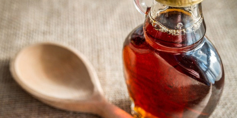 A jar of maple syrup and a wooden spoon on a table