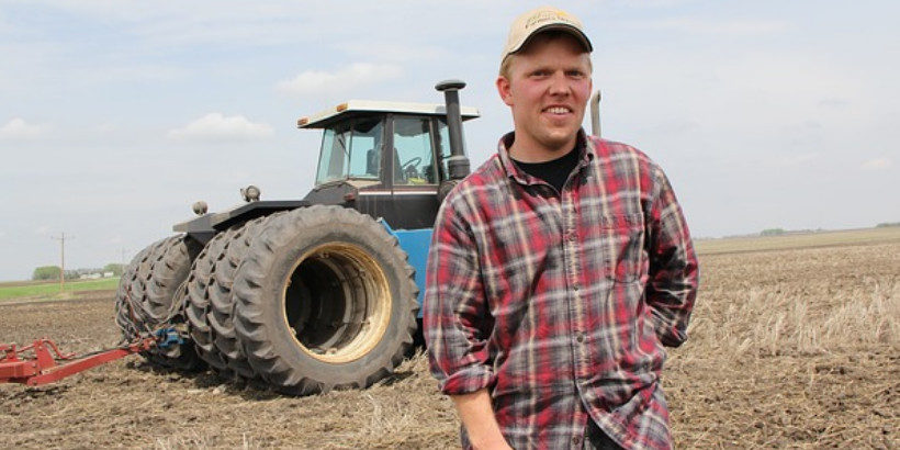 Farmer standing in front of a tractor in a field