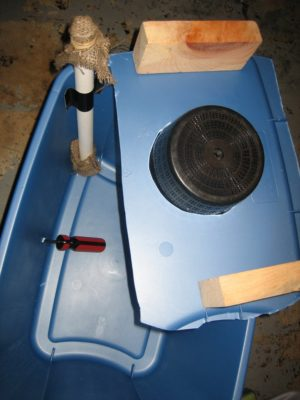 pipe and wood blocks on plastic bin