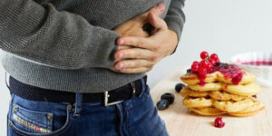 man holding stomach next to pancakes on counter