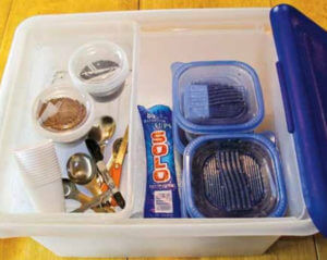 Plastic box containing seeds, scissors, measuring spoons, and cups